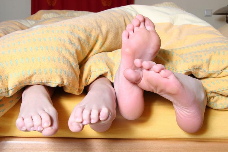 Dva páry nôh trčia spod žltého paplóna