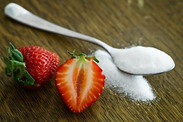 Lyžička bieleho cukru a rozpolená jahoda položené na drevenom stole