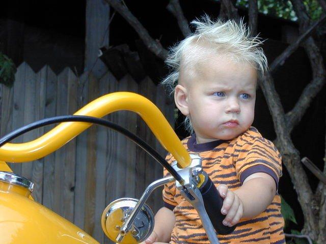 Malý chlapec sediaci na motorke