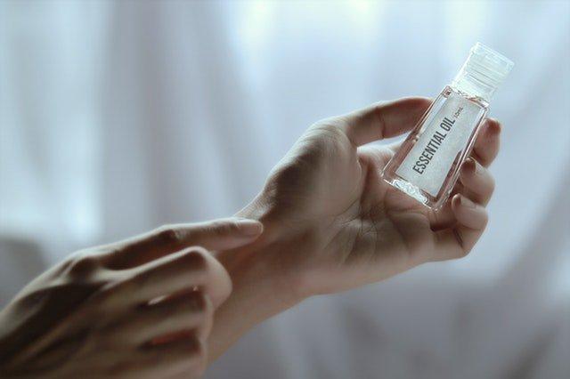 Žena drží v rukách fľaštičku s esenciálnym olejom.jpg