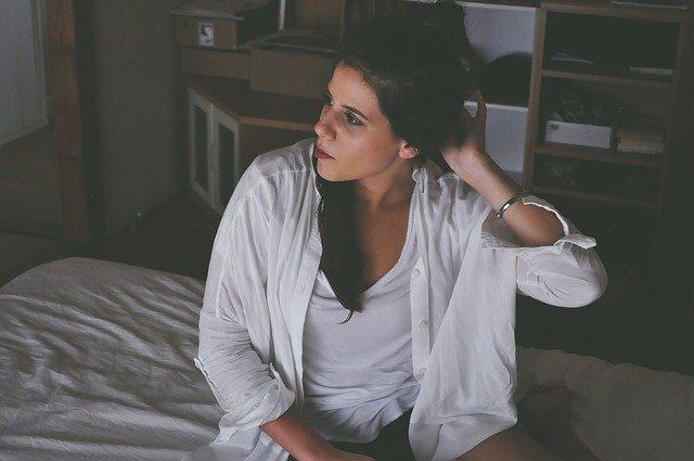 Žena v bielom tričku a v bielej košeli sedí na posteli.jpg