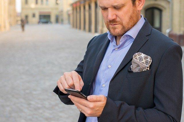 Muž v tmavom obleku stojí na ulici a ťuká do telefónu.jpg